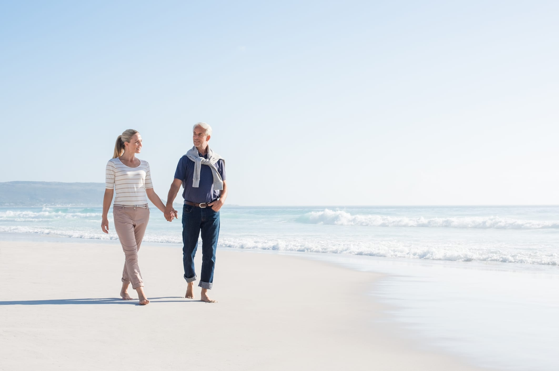 Senior couple holding hands at the beach on a bright sunny day. Mature couple in love holding hands and looking each other at the seaside. Smiling wife and happy husband walking barefoot on the white sand.