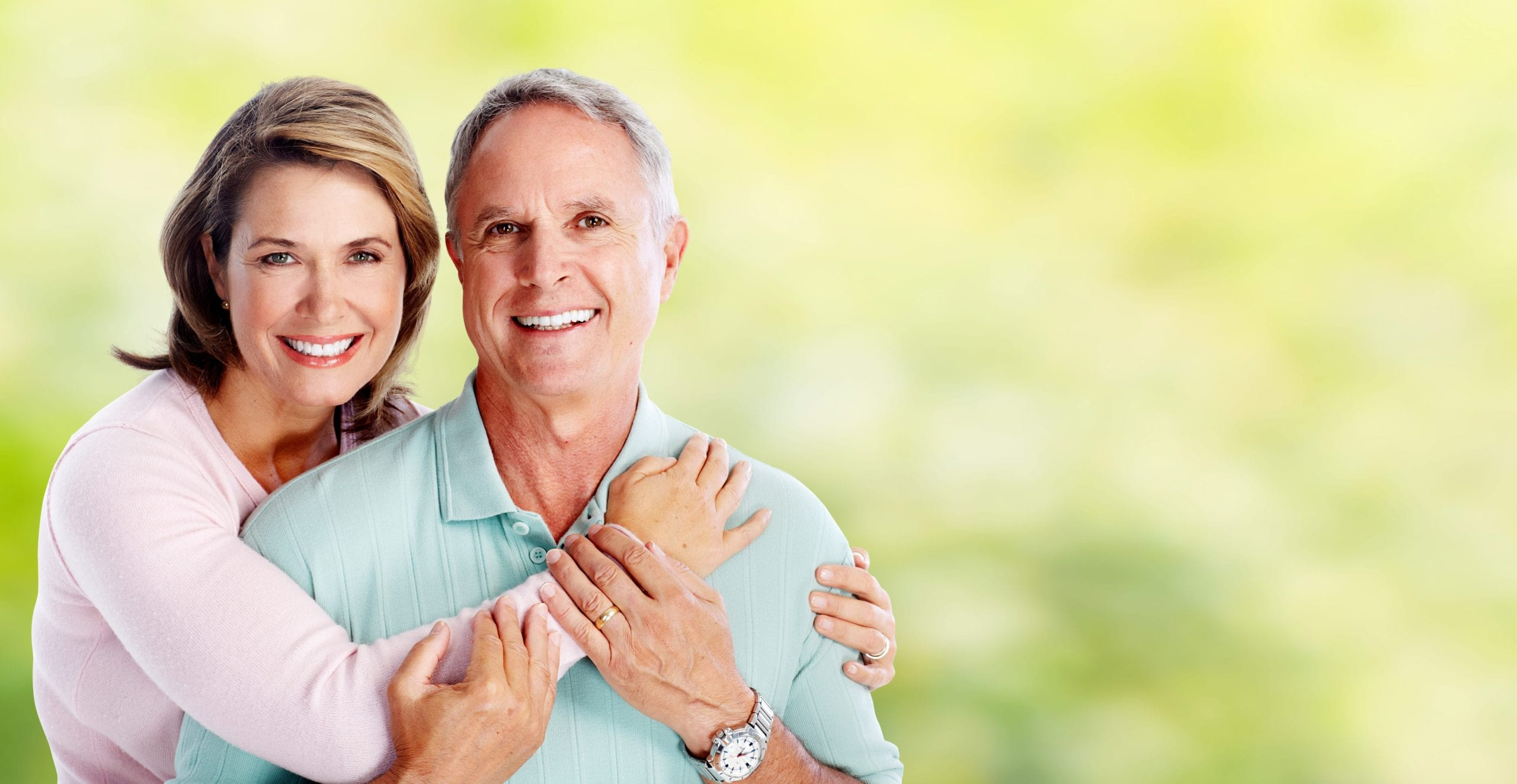 Happy senior loving couple over green nature background
