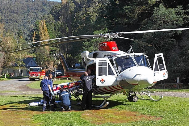 Walhalla, Australia - April 25, 2014: The crew of the Air Ambulance Victoria helicopter Helimed 1 supervise the transfer of an accident victim from ambulance to helicopter on the Anzac Day holiday in a small remote hillside town in rugged countryside.  The ambulance paramedics and doctor assist loading the stretcher onto the waiting chopper.  In the background, the local volunteer fire brigade officer has stationed the fire truck to protect the helicopter landing pad