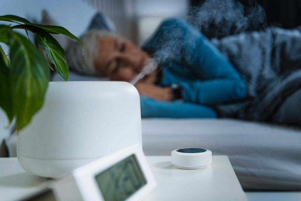 Woman sleeping in bed with an alarm set and air mist diffuser on