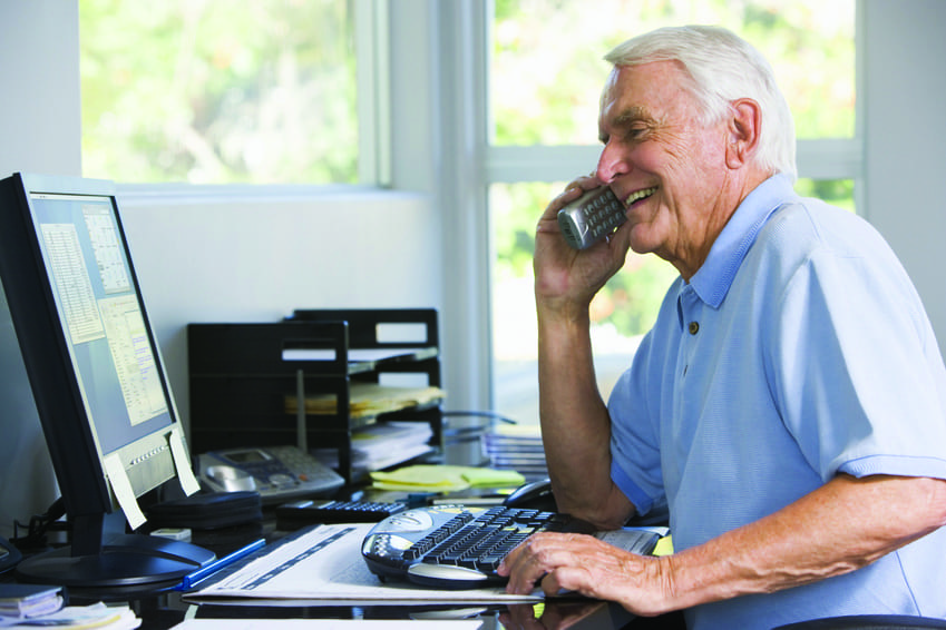Man in home office on telephone using computer